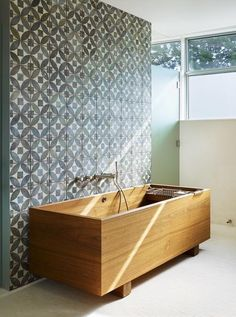 This deep wooden tub has a more familiar rectangle shape. I love the look of this warm wood tub next to the more intricately patterned tiles.
