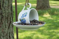 Hanging toppled teacup bird feeder -- what a *darling* favor this would make for a garden-themed tea party!!  Instead of leaving the seed loose, you could put a healthy handful in a circle of tulle, tied with a pretty ribbon.  FUN!  :)