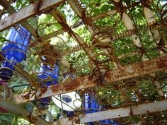 interesting ceiling of recycled bedsprings & blue bottles by marian