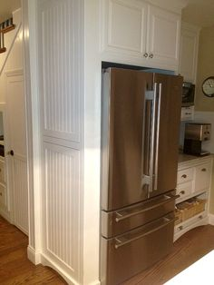 Cabinet surround around refrigerator that hides bulletin boards, phone chargers & reminder notices, all in a slim cabinet next to the fridge. It's paneled to look like beadboard walls, but they open up with touch latches. Above fridge are divided tray holders for cookie sheets and bakeware.
