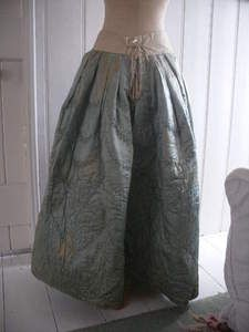 "c. 1740-1770's QUILTED SILK PETTICOAT ""It is light blue silk, hand-quilted with a design which includes carnations (or pinks). The quilted silk part is gathered onto a cotton waistband & the inner fabric is more coarsely woven. The waistband may be a later, Victorian alteration. It fastens with ties at the back & there is a slit in the side seam so this could be used with a separate, tie-on pocket."""