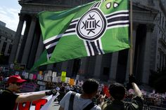 A Kekistan flag at an anti-Muslim rally in New York on June 10, 2017. Military contractor fired for wearing neo-nazi symbol. HuffPost, 20180925.