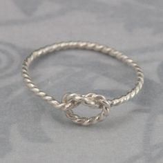 This adorable ring is hand forged in 1.3mm diameter (16 gauge) round solid sterling silver twist wire. It features a knot design in the front and is high polished. It is perfect as a friendship ring or promise ring...and super cute on any finger! Give one to your friends who helped you tie the knot!  Please dont hesitate to contact us with any questions or concerns. All of our jewelry is handmade by either myself or my brother Bryan. We are a small family business that prides itself on our…