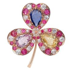 Antique diamond, ruby, and sapphire clover pin, each heart-shaped leaf set with a colored sapphire (blue, pink and yellow) center with a diamond and ruby alternate surround, mounted in pink gold, circa 1870.