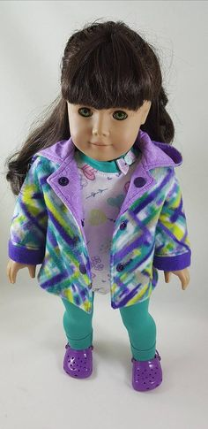 Fleece hooded jacket in shades of purple and jade is made to fit 18 inch dolls. The jacket is lined with 100% cotton purple print and has purple fleece cuffs with purple decorative snaps for the front closure. This is shown over a two piece tunic and leggings. The long sleeve tunic is