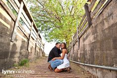 Country chic engagement portraits.  Rustic alley. Cowboy boots.