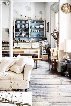 Cozy living room with bare wood floors,  columns, and a vintage china cabinet