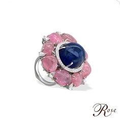 A versatile ring crafted with a beautiful Tanzanite Cabochon nestled in Pink Tourmalines and fancy Diamonds set in 18K White Gold