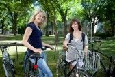 Beautiful_bike : Young female students standing with bicycle at college campus lawn Stock Photo