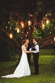 Wedding decor lanterns in trees for ceremony backdrop