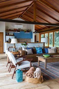 Decoração de casa de campo com madeira. Na sala sofá marrom, almofadas azuis, mesa de centro de madeira com adornos, poltrona de madeira com estofado branco, tapete listrado, cesto.