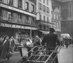 """Paris, la rue Coquillière, devant le célèbre restaurant """"Au Pied de Cochon"""", vers 1955. L'activité des Halles tôt le matin près de la """"Pointe Saint-Eustache"""". Les Halles qui avaient encore plus ou moins 15 ans à vivre... Une photo de Janine Niépce."""