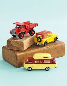 toy trucks and a van on wooden blocks - cute table decoration and trucks can be great goodie bag items after party