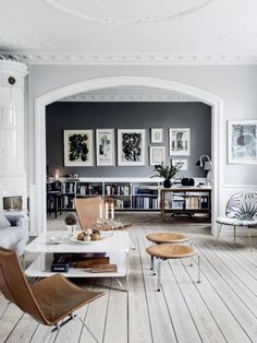 Beautiful, Scandinavian living area with light hardwood floors, leather accents, an arched doorway and framed prints | Photos for Elle DK