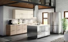 A kitchen with a combination of stainless steel, light-wood and high gloss white cabinet doors