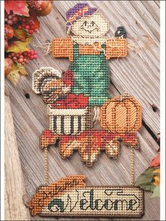 """Autumn Welcome  ~~   Welcome friends and family into your home with this cheery scarecrow surrounded by autumn bounty!     Technique - Plastic Canvas  This e-pattern was originally published in the October 2001 issue of Plastic Canvas Crafts.   FINISHED Size: 7"""" x 13 1/4"""".  Made with plastic canvas yarn, #3 and #5 pearl cotton, 6-strand embroidery floss and 7-count plastic canvas.   Skill Level: Intermediate"""