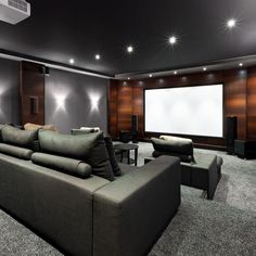 Home theater with stadium seating with sofas in dark grey color scheme and wood panel wall.: