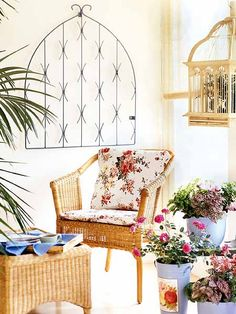 an outdoor space is decorated with floral fabric and a painted iron gate
