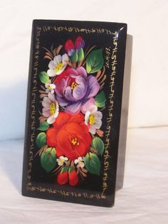 This is a beautifully hand painted russian lacquer trinket box which is signed on the bottom of the box. The box depicts a beautiful floral arrangement. It is entirely hand painted with no stencils.