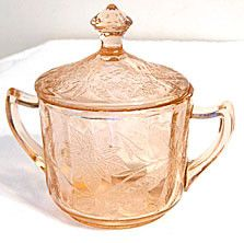 Here is a Depression Glass sugar bowl with original lid in the Floral pattern that was made by Jeannette. It measures 5.5 inches wide including the handles and 5.25 inches high. This piece is in very