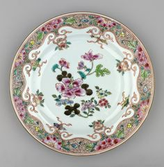 A Chinese famille rose porcelain plate painted at the centre w a hibiscus spray; scrolling rim border w pendant emblems & buds enclosing peony & other pink blooms upon a brown spiral ground.