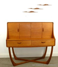 Mid Century Teak Credenza by Beithcraft, Scotland. The credenza stands on elegant crossed legs. Two drawers and shelves hidden by folding doors. £1,450