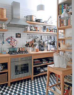 La cocina es casi industrial y sencilla: muchos objetos a la vista o sobre repisas y muebles de madera.