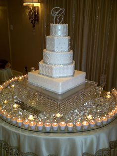 Decoración de torta de boda con una muy bonita base y velas.