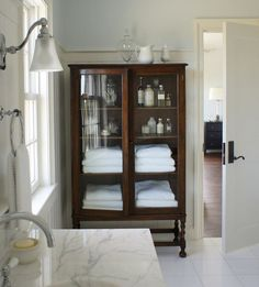 I love antique cabinets in bathrooms for toiletries and towels. So gorgeous