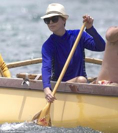 Water babe: Charlize Theron shows off her oar skills as she enjoys a spot of kayaking while on holiday in Hawaii wearing a Coolibar Long Sleeve Swim Shirt.