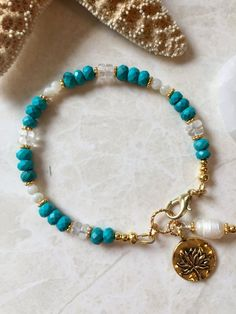 Turquoise crystal quartz and mother of pearl bracelet with lotus flower charm Diy Jewellery Designs, Jewelry Trends, Jewelry Design, Ankle Bracelets, Jewelry Bracelets, Jewelery, Pearl Bracelet, Crystal Necklace, Turquoise Jewelry