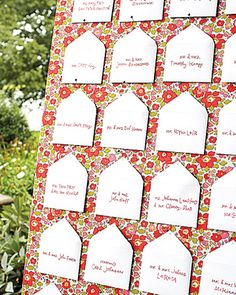 Miniature envelopes holding stamped table assignments were pinned to a fabric-covered board propped on an easel on the lawn.