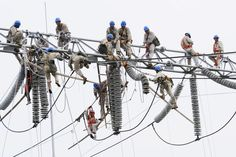 HIGH WIRE WORK: Workers climbed onto equipment to perform maintenance work at an electric power substation in Xuzhou, China, Friday. (China Daily/Reuters)