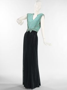 Evening Dress 1932 After the Stock Market Crash of 1929, the era of the flapper was put to rest, the hemlines dropped and the waistline rose. A slim figure was still in vogue but this was accented by the bias-cut dress, low backs, and deep V-necks at front. The 1930s was full of glamour and with the growing popularity of the cinema, women turned to their favorite actresses for wardrobe inspiration. This evening dress evokes the idea of a chic evening. The bodice construction is inventive…