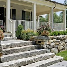 Stone set stairs welcome visitors to a cozy covered porch