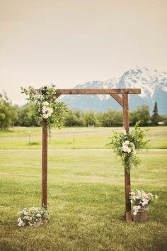 The wooden altar was dressed with lush arrangements featuring white roses, eucalyptus and other greenery. Venue: Paradise Alaska Event Coordinator: Blomma Desig
