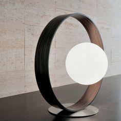 Lampe à poser de la collection Giuko, composée d'un large anneau en ébène sur un socle en aluminium satiné, supportant à mi-hauteur un globe en verre soufflé satiné.