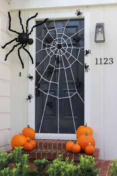 A festive Halloween door decoration with a DIY giant spider web and spiders big and small crawling all over the door!