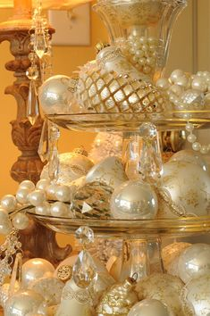 Great holiday table centerpiece - stacked cake plates filled with ornaments, pearls, pretty baubles and hanging crystals.