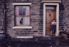 A girl stands in a doorway, Manchester, England, United Kingdom, 1965, photograph by John Bulmer.