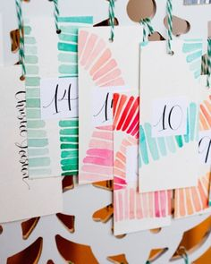 Escort cards made from large watercolor paintings that were then cut into tags and calligraphed