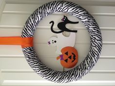 Halloween wreath for Leah's door! - pool noodle - zebra print ribbon - orange ribbon - glitter paper to make the characters