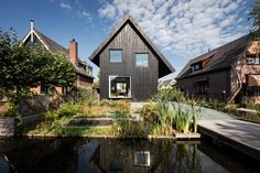 Chris Collaris Architects builds black wooden cottage with exaggerated roof