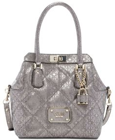 """GUESS Ophelia Quilted Satchel Logo Embossed (Pewter). Quilted textured faux-leather exterior with G-shine print; Shiny pale Silver-tone hardware. Triple compartment design with center snap ce, signature closure. Exterior features pale shiny Silver-tone hardware, logo plaque, padlock charm, 1 back slip pocket and 2 top zip compartments. Interior features 1 zip pocket and 3 slip pockets. Approx. 11"""" W x 10"""" H x 5.25"""" D. Double handles with 5"""" drop; detachable strap with 23"""" drop."""