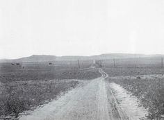 "Austin Bluffs Road, a rutted path of dirt, year unkown.  Bluffs visible in background.  On left are several ""powder houses"" where blasting powder was stored."