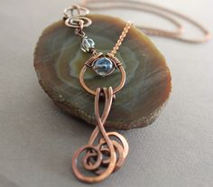 Swirly copper pendant  necklace in hoop design with swirl dangles and light blue quartz with decorative hook clasp