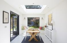 Large patio doors, a crittal-style window seat and skylights create a striking and light-filled dining space at the back of the new kitchen extension of this family home. Kitchen Diner Extension, Rear Extension, Patio Doors, New Kitchen, French Doors, Home And Family, Dining Table, Windows, Interior Design