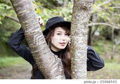 兵庫県武田尾の廃線跡のハイキングコースの桜の木の間から顔を出す帽子をかぶった若い女性