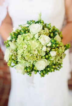 A mostly green bouquet comprised of hydrangeas, hypericum berries, and roses, created by Rodney Meek.