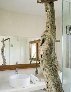 Para potenciar la luz del cuarto de baño, que penetra a través de dos ventanas, se pintó de blanco esta Casa-Cabaña en Uruguay ... En el cuarto de baño destaca un enorme tronco que se ha encastrado en el suelo de cemento pulido y que sirve de toallero